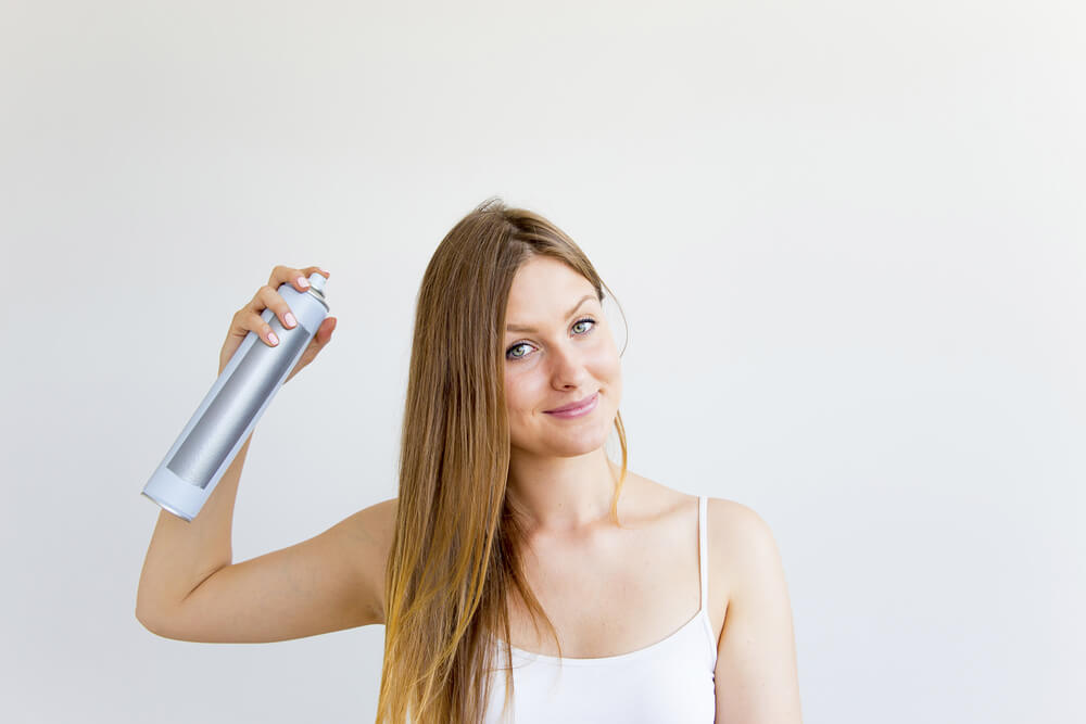 Woman holding dry shampoo bottle to her hair