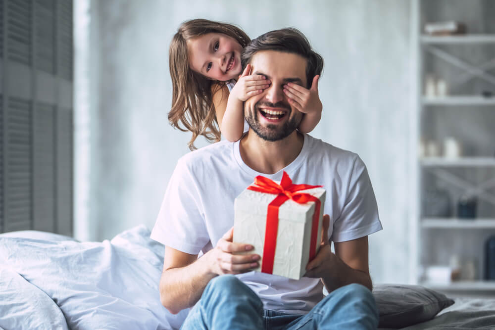 girl gives her dad a gift while holding his eyes closed