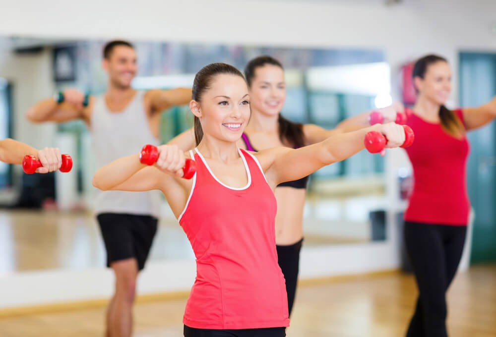woman in workout class lifting weights