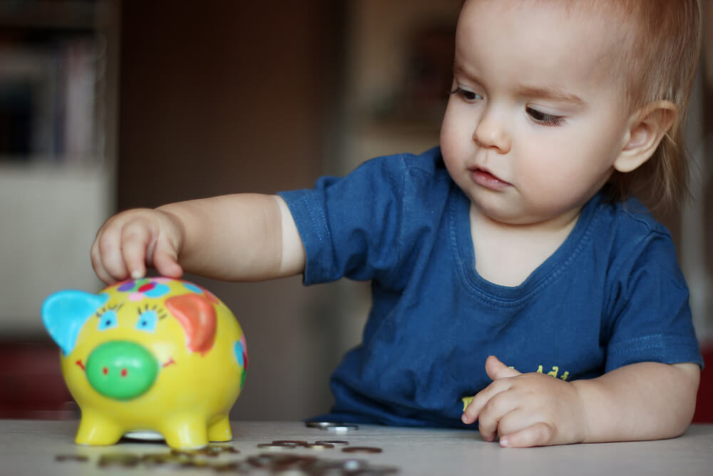 Baby putting coins into piggy bank