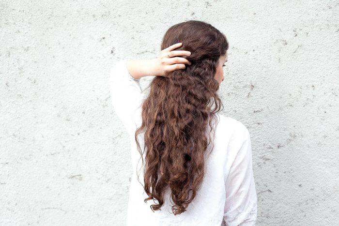 woman facing backwards with long dark curly hair