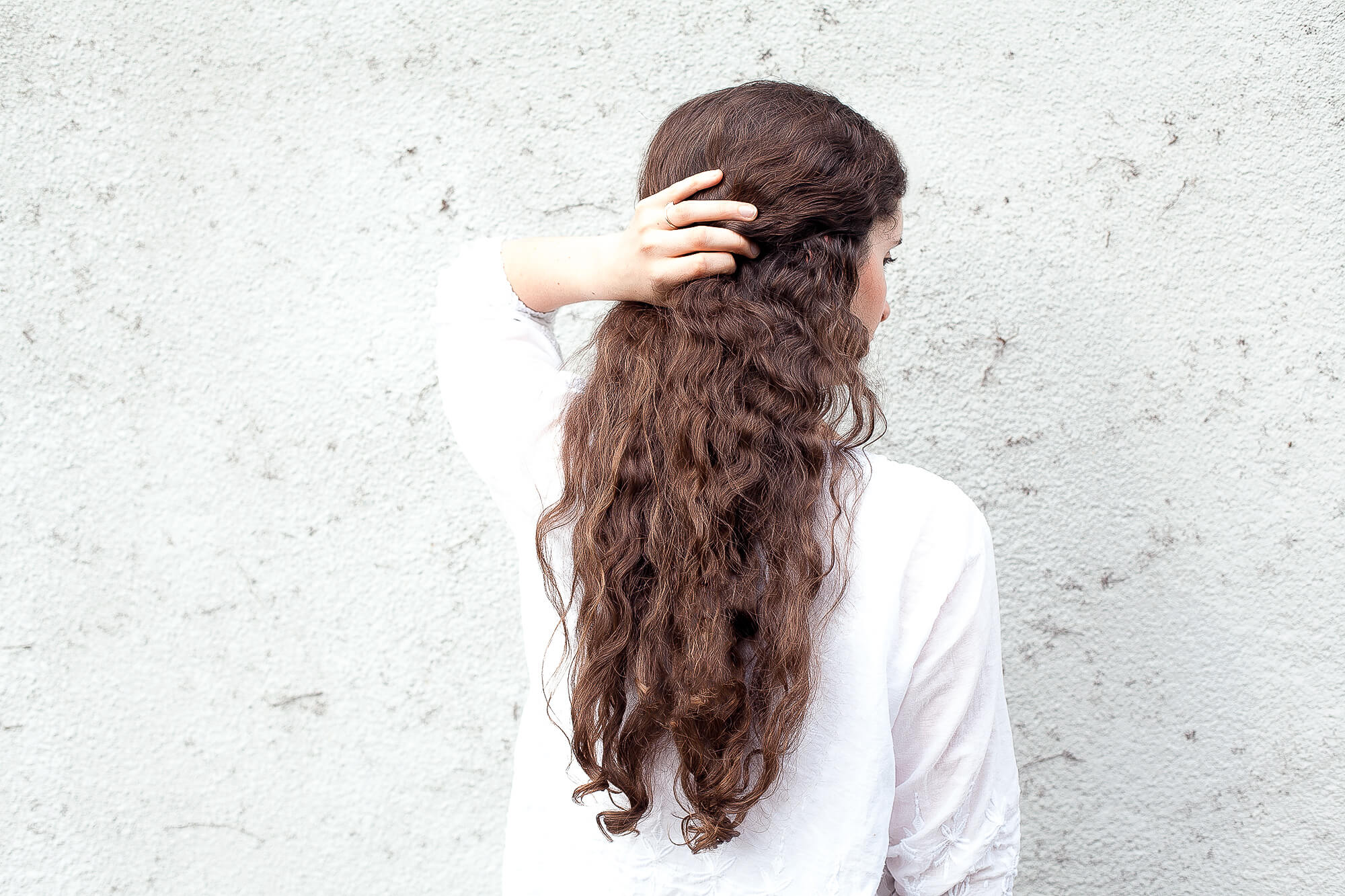 woman facing backwards with long dark curly hair