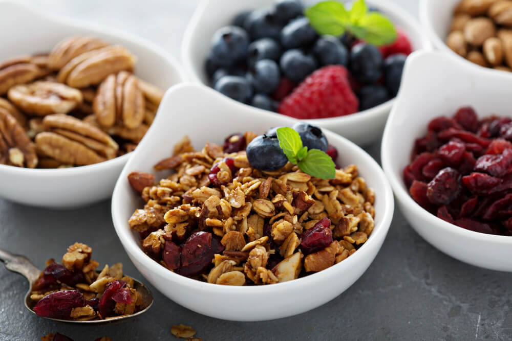 Small bowls of berries, nuts and granola
