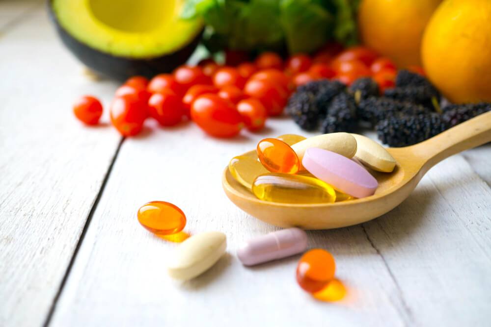 Vitamin supplements on a spoon with fruits and veggies in the background