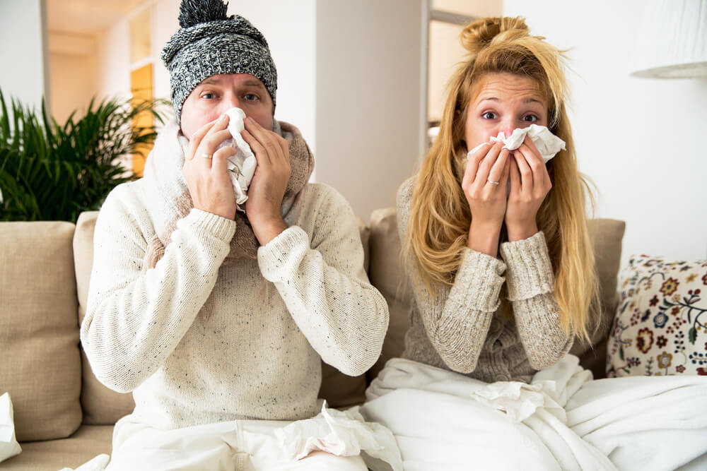 Man and woman sneezing while sitting on couch