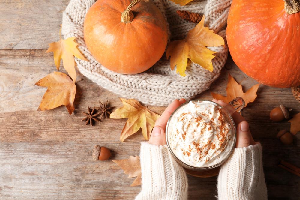 Female hands holding a latte beside a pumpkin