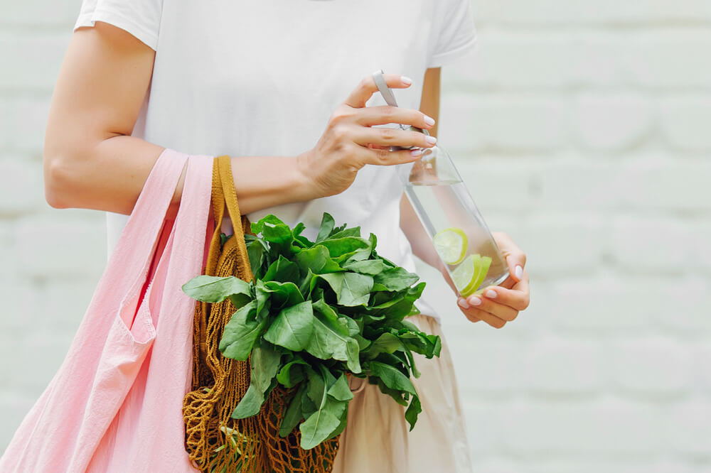 woman holding reusable bag and produce