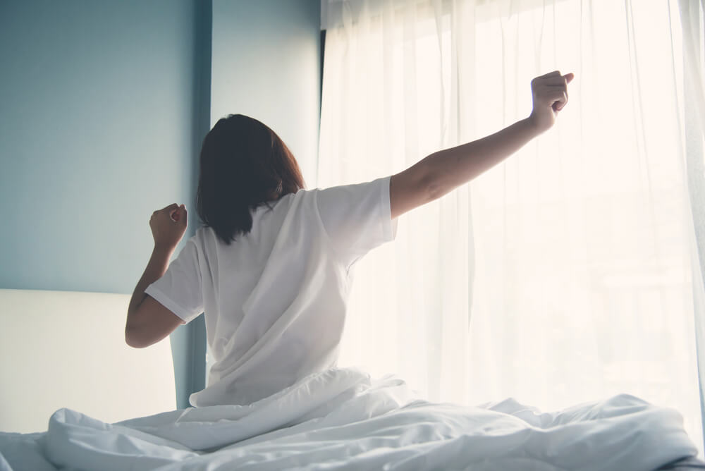 woman stretching as she gets out of bed