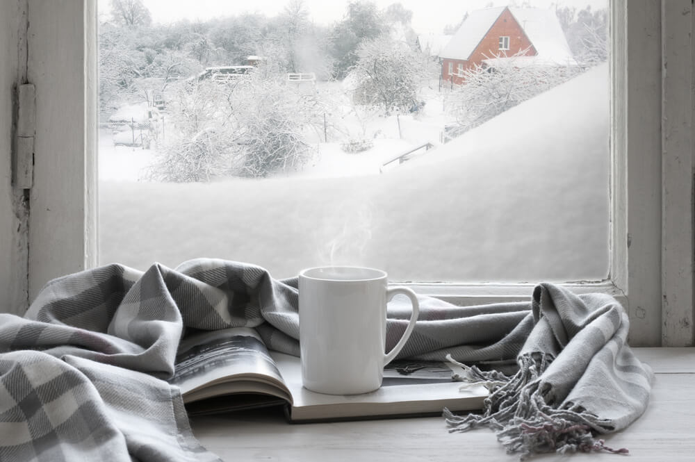 grey scarf and white mug by a winter window