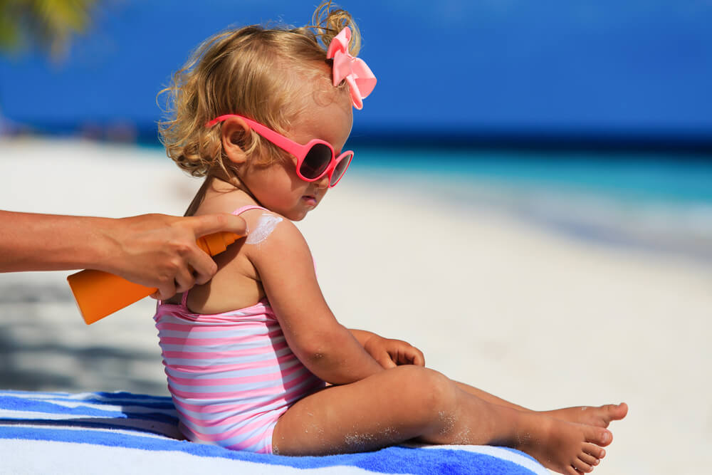 mother applying sunscreen to young girl