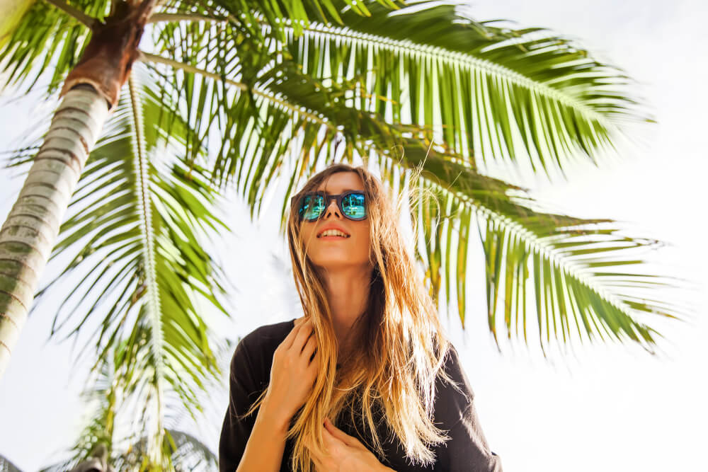 palm treat with young woman wearing sunglasses