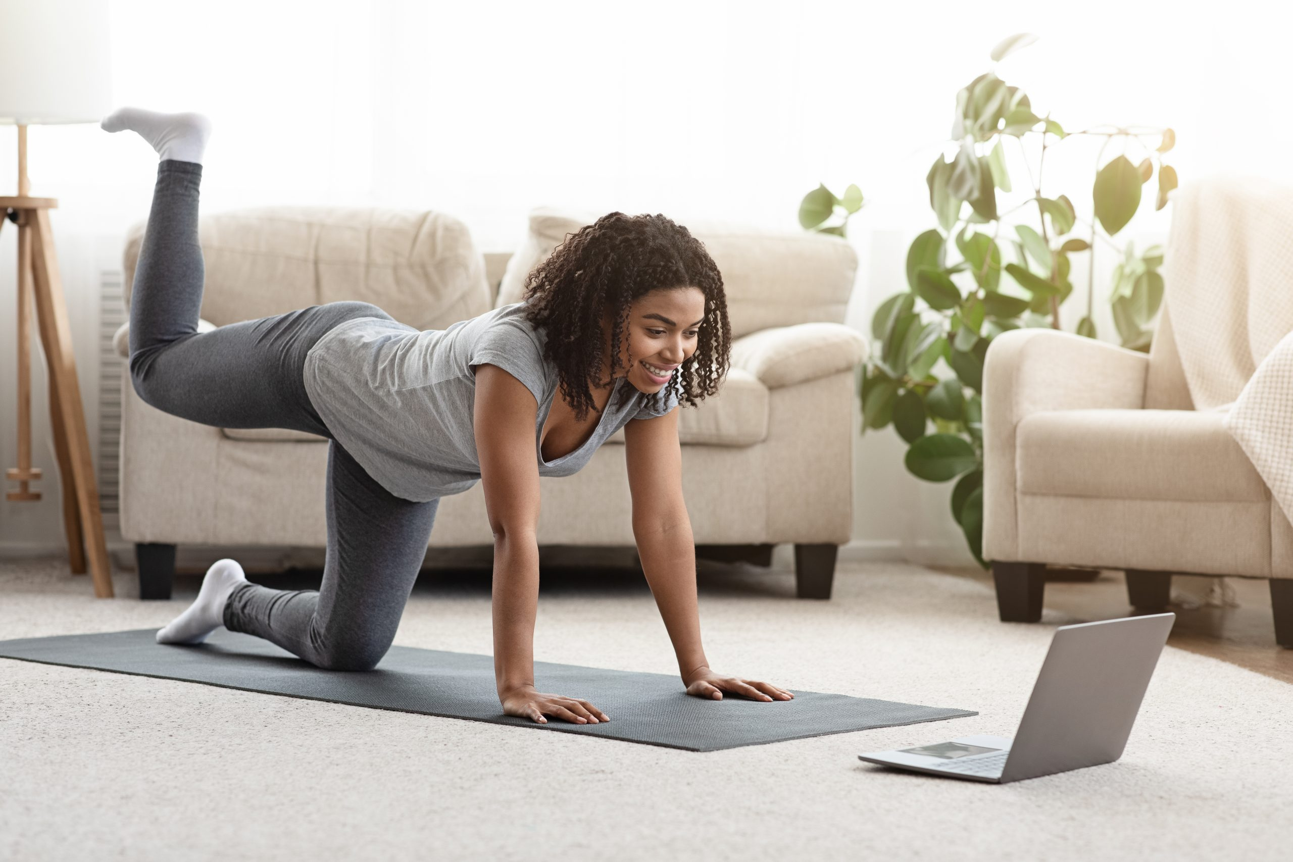 woman working out in her living room on a yoga mat looking at a laptop