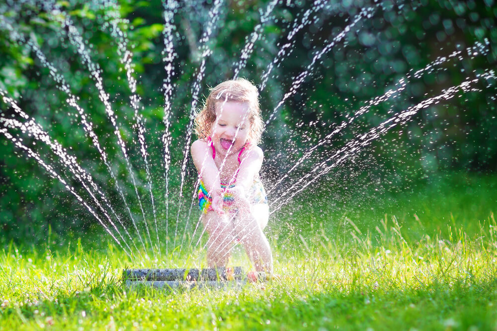 young girl in sprinkler