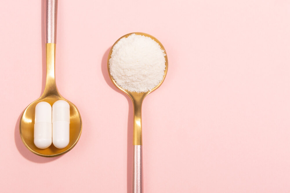2 gold spoons one with powdered collagen and one with pills