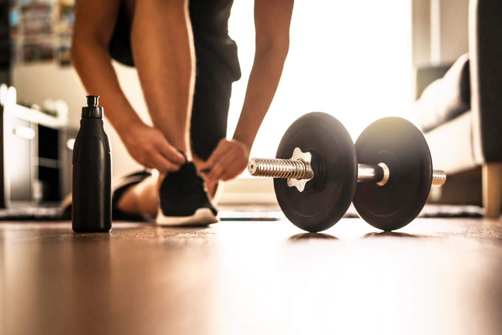 person lacing up their shoe near a dumbell and a waterbottle