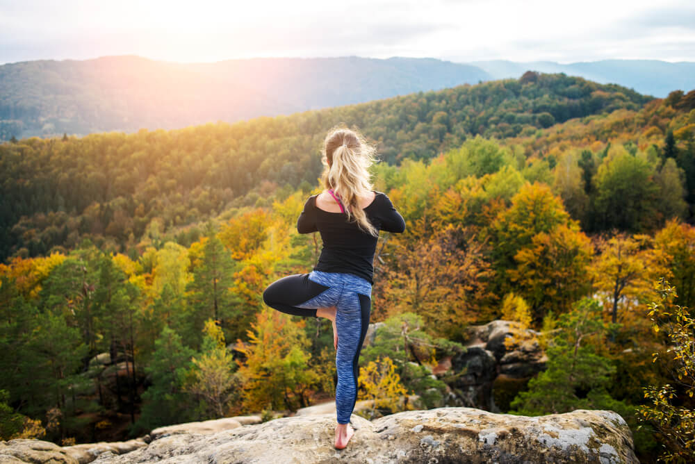 woman in tree pose on a cliff with fall trees int he distance
