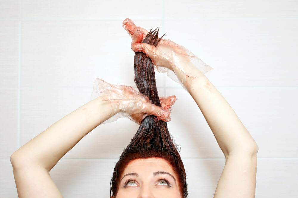 woman colouring her hair in the shower