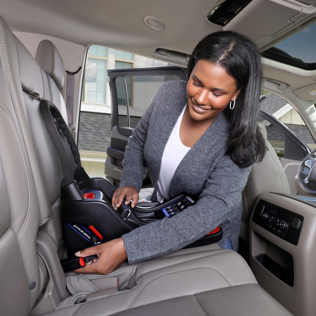 Mother clipping in base of car seat