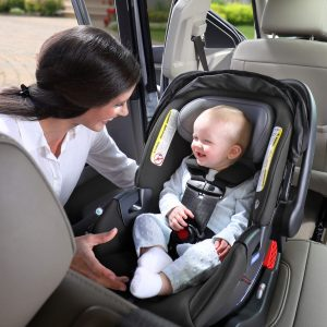 Mother smiling at baby in car seat