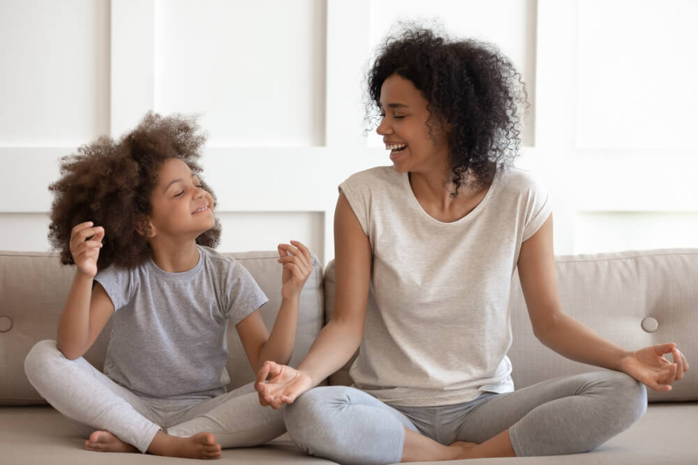 woman and daughter meditating on a couch